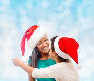 Happy mother and girl in santa hats Royalty Free Stock Photography