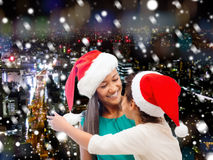 Happy mother and girl in santa hats Stock Images