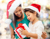 Happy mother and girl in santa hats with gift box Royalty Free Stock Photo