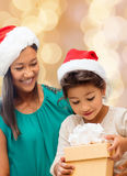 Happy mother and girl in santa hats with gift box Royalty Free Stock Images