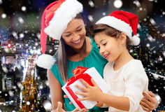 Happy mother and girl in santa hats with gift box Stock Image