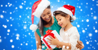 Happy mother and girl in santa hats with gift box Stock Photos