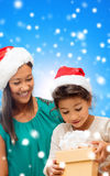 Happy mother and girl in santa hats with gift box Stock Photo