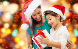 Happy mother and girl in santa hats with gift box Stock Images