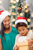 Happy mother and girl in santa hats with gift box Stock Photography