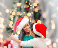 Happy mother and girl in santa hats Royalty Free Stock Photos