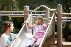 Happy mother with  girl on slide Royalty Free Stock Photo