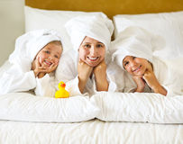Happy mother and girls in bathrobes on bed Stock Images