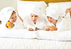 Happy mother and girls in bathrobes in bedroom. Family care and Stock Images