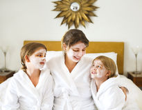 Happy mother and girls in bathrobes with cream mask Stock Photos