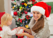 Happy mother giving baby Christmas cookies Stock Photography