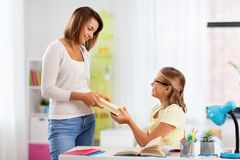 Happy mother giving daughter book at home stock images