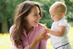 Happy mother giving flower to baby in the park royalty free stock photos