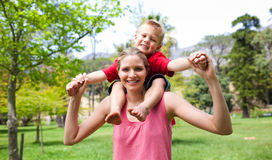 Happy mother giving her son a piggyback ride. In a park Stock Image