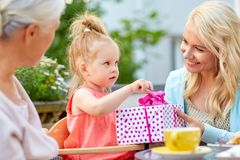 Happy mother giving present to daughter at cafe Stock Photo