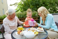 Happy mother giving present to little daughter at cafe Royalty Free Stock Images