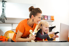Happy mother with halloween dressed daughter having video chat Stock Photos