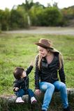 A happy mother in a hat emotionally tells something of her baby. Sitting on a log Stock Images