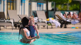 Happy mother have a good time with her daughter in the swimming pool stock footage