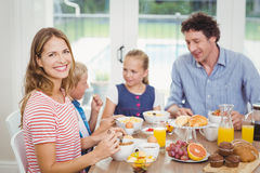 Happy mother having breakfast with family at table Royalty Free Stock Photo