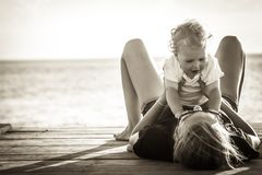 Happy mother having fun with her child baby lying on back on pier with sunlight during summer beach holidays in black and white Stock Photo