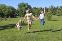 Happy mother having fun jumping with her daughters on green grass stock photography