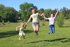 Happy mother having fun jumping with her daughters on green grass stock images