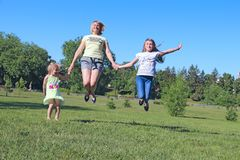 Happy mother having fun jumping with her daughters on green grass. Happy family team. Family enjoying summer vacations. People stock images