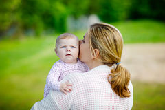 Happy mother having fun with newborn baby daughter outdoors royalty free stock photography