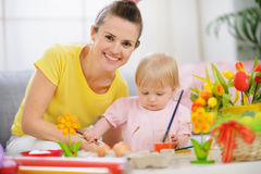 Happy mother helping baby painting on Easter eggs Stock Photography