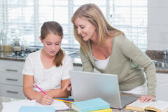 Happy mother helping daughter doing homework Stock Photos