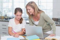 Happy mother helping daughter doing homework Stock Photos
