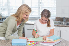 Happy mother helping daughter doing homework Stock Images