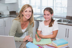 Happy mother helping daughter doing homework Royalty Free Stock Photography