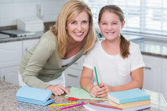 Happy mother helping daughter doing homework Royalty Free Stock Images