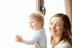 Happy Mother with her baby boy looking at the window Stock Photography