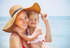Happy mother and her baby daughter on sea coast Stock Images