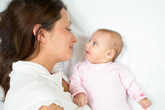 Happy mother and her baby girl looking each other Stock Images