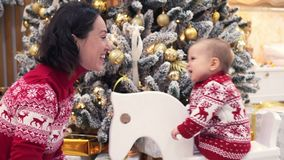 Mother with baby girl on rocking deer toy during Christmas eve stock video footage