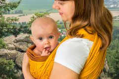 Happy mother with her baby in a sling Royalty Free Stock Photography