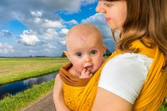 Happy mother with her baby in a sling royalty free stock photo