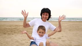 A happy mother and her baby are smiling, waving their hands towards the camera, sitting on a sandy beach, against the stock video
