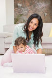 Happy mother with her baby using laptop Royalty Free Stock Photo