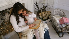 Happy mother and her beautiful daughter in white sweaters reading a book on Christmas eve stock video footage