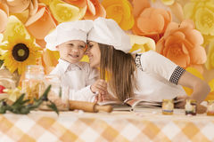 Happy mother and her child in the form of chefs prepare a festiv. Happy mother and her child in the form of chefs preparing dinner. On a floral background stock photos