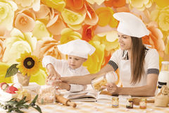 Happy mother and her child in the form of chefs preparing dinner Stock Photography
