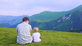 Happy mother and her child looking forward and pointing to sky. Family on trekking day in the mountains. Royalty Free Stock Photography