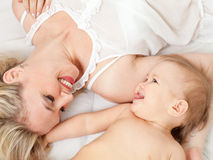 Happy mother and her child are lying together. Loving mother and her child near each other Royalty Free Stock Image