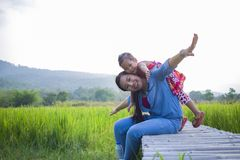 Happy Mother and her child play outdoors having fun, Green  rice field back ground royalty free stock images