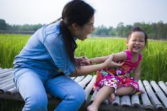 Happy Mother and her child play outdoors having fun, Green  rice field back ground stock photo